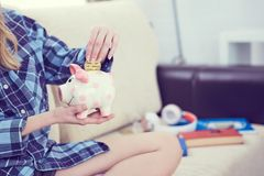 Young girl sitting on couch and putting litecoin in piggybank. royalty free stock photo
