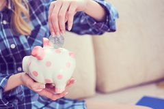 Young girl sitting on couch and putting litecoin in piggybank. royalty free stock image