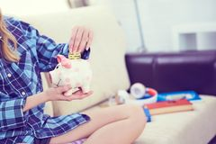 Young girl sitting on couch and putting litecoin in piggybank. royalty free stock photography