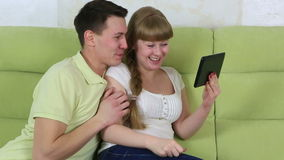 Young girl sitting on couch and talking on Skype on the tablet. Her boyfriend sits down and continues to participate in stock video footage