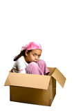 A young girl sitting cramped in a box. Concept of pressure, constraints and lack of freedom. Isolated on white royalty free stock images