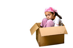 A young girl sitting cramped in a box. Concept of pressure, constraints and lack of freedom. Isolated on white stock image
