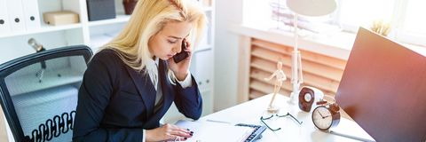 Young girl sitting at desk in office, talking on phone and looking at documents. A slender young girl in a white blouse and blue jacket is working in the office royalty free stock image