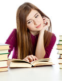 Young girl sitting at the desk and reading book. Royalty Free Stock Photo