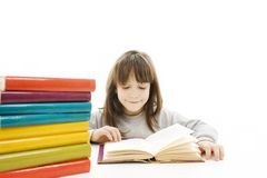Young girl sitting at the desk and reading book. Stock Images