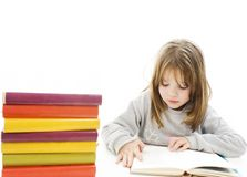 Young girl sitting at the desk and reading book Royalty Free Stock Image