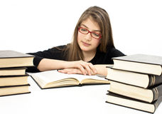 Young girl sitting at the desk and reading book Stock Photo