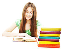 Young girl sitting at the desk and reading book Royalty Free Stock Photography