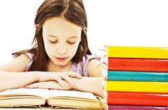 Young girl sitting at the desk and reading book Stock Images
