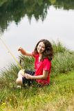 Young Girl Sitting Down and Catching Fish on the Lake Stock Photo