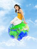 Young girl sitting on earth globe in clouds Stock Photo