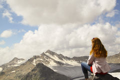 Young girl sitting on the edge of a cliff and looking at the sky Royalty Free Stock Images