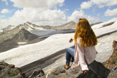 Young girl sitting on the edge of a cliff and looking at the sky Stock Photography