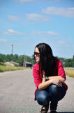 Young girl sitting on the edge of the road. The dark-haired woman sitting on the edge of the road in the afternoon Stock Photography