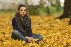 Young girl sitting on fallen leaves in the autumn park. Walking. Young girl sitting on fallen leaves in the autumn park royalty free stock photo