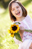 Young Girl Sitting In Field Holding Sunflower Royalty Free Stock Photo