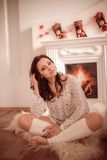Young girl sitting beside the fireplace Stock Photography