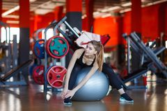 Young girl sitting on fitness ball in modern hall. royalty free stock photos