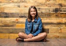 Young girl sitting on floor Stock Photo