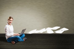 Young girl sitting on the floor with a laptop Royalty Free Stock Images