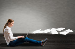 Young girl sitting on the floor with a laptop Stock Photos