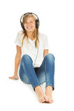 Young girl sitting on the floor listening to music over white ba Royalty Free Stock Images