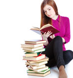 Young girl is sitting on a floor and reading book Stock Photography