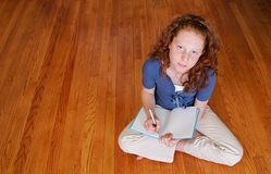 Young girl sitting on the floor writing Royalty Free Stock Images