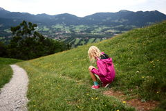 Young girl is sitting in a flower field Stock Photography