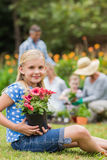 Young girl sitting with flower pot Stock Images