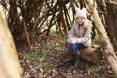 Young girl sitting in a forest shelter made of tree branches Stock Image