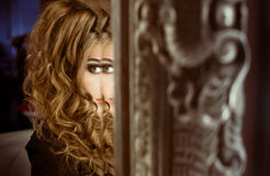 A young girl sitting in front of a big mirror and looking away o Stock Photography