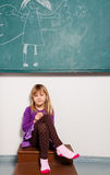 Young girl sitting in front of chalkboard Stock Images