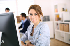 Young girl sitting in front of computer Stock Images