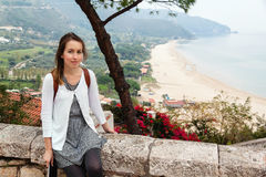 Young girl sitting in front of panoramic view of Sperlonga Royalty Free Stock Image