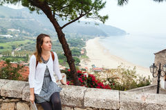 Young girl sitting in front of panoramic view of Sperlonga Stock Photos