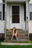 Young girl sitting on front steps on house Royalty Free Stock Photos