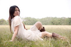 Young girl sitting on the grass. And staring at far away Royalty Free Stock Image
