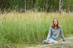 Young girl sitting in the grass Royalty Free Stock Photography