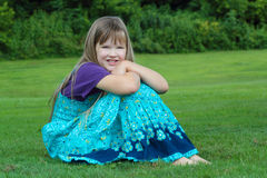 Young girl sitting in grass stock photo