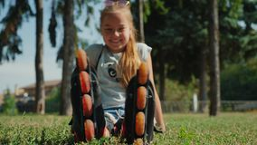 Young girl sitting on the grass admiring roller skates. Young girl sitting on the grass in a city park smiling, admiring roller skates stock footage
