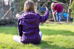 Young girl sitting on the grass and doing photo at the working w Stock Images