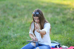 Young girl sitting on the grass in the park and works at a laptop and eating fast food Stock Images