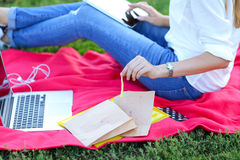 Young girl sitting on the grass in the park and works at a laptop and eating fast food Stock Photos