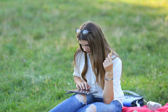 Young girl sitting on the grass in the park and works at a laptop and eating fast food Stock Photo