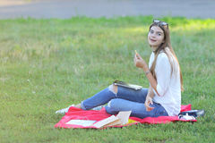 Young girl sitting on the grass in park and works at a laptop eating fast food Royalty Free Stock Image