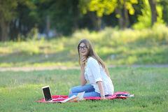 Young girl sitting on the grass in the park and works at a laptop. Royalty Free Stock Photos