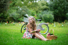 Young girl sitting on the grass and reading a book Royalty Free Stock Photography