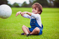 Young girl sitting on a grass throwing ball Royalty Free Stock Image