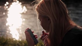 Young girl sitting on the gren grass near the river at sunset and applies lipstick looking at the phone screen stock video footage
